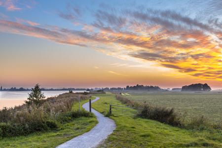 Photo pour Holland Polder landscape with winding cycling track along river under beautiful sunset - image libre de droit