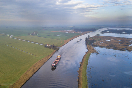 Photo pour Aerial view of canal in Friesland with inland freight ships passing by. The Netherlands - image libre de droit