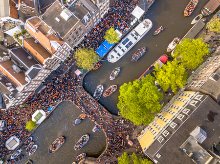 Photo pour Canal boat parade on Koningsdag Kings day festivities in Amsterdam. Birthday of the king. Seen from helicopter. - image libre de droit