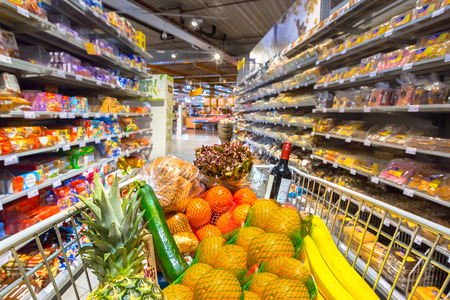 Foto für Grocery cart in supermarket filled with food products seen from the customers point of view - Lizenzfreies Bild