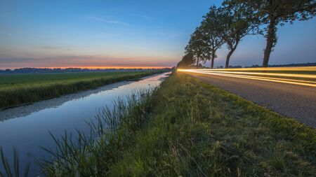 Photo pour Netherlands open polder landscape with canal and traffic lights on road in open grassland countryside at sunset - image libre de droit