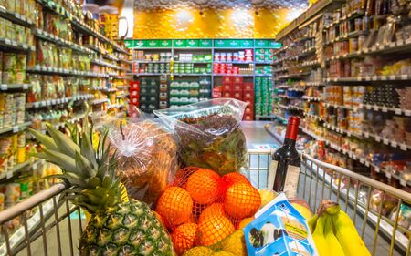 Photo pour Grocery cart in supermarket filled with food products seen from the customers point of view - image libre de droit
