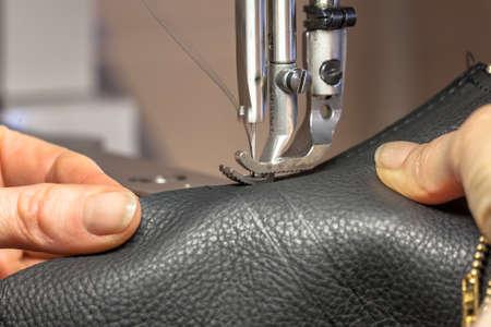 Foto für Leather Sewing machine in action in workshop operated with hands working on garment - Lizenzfreies Bild