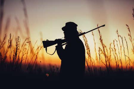 Hunter holding shotgun on shoulder and observing land in sunrise. High grass is sourrounding him