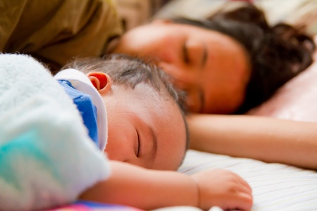 Asian female baby sleeping with her mother on bed