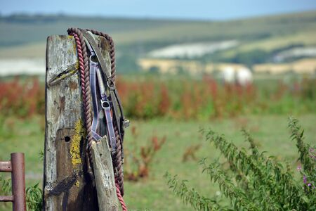 Riding tack hanging off an old wooden gatepost