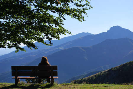 Woman sitting on a bench in front of mountains panorama, Alps, Piedmont, Italy