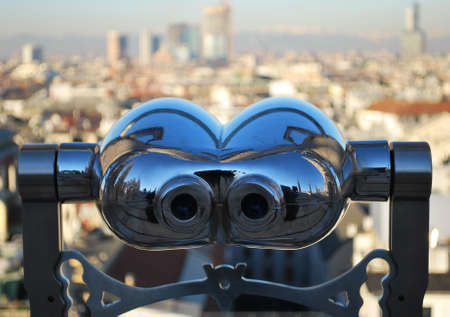 Binoculars telescope looking Milan panorama from the roof of the Duomo cathedral, Lombardy, Italy