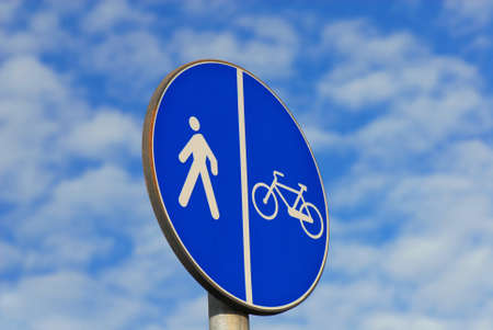Pedestrian and bicycles area road sign against cloudy sky