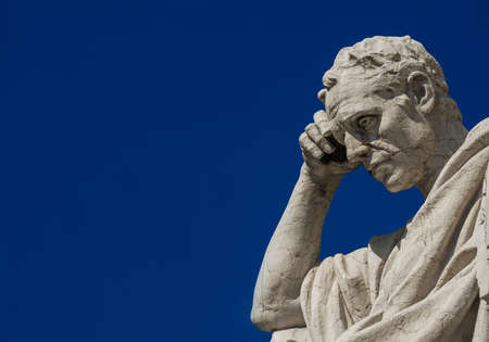 Man statue in the act of thinking against blue sky. Ancient Roman Julian the Jurist statue erected at the end of 19th century in front of the Old Palace of Justice in Rome (with copy space)