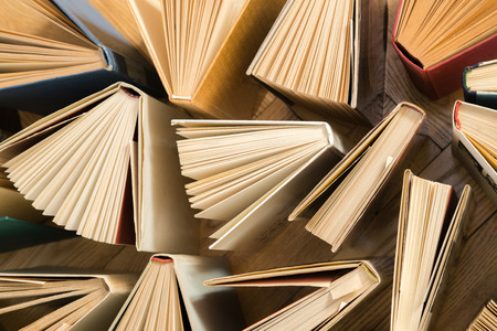 Photo pour Old and used hardback books, text books seen from above on wooden floor. Books and reading are essential for self improvement, gaining knowledge and success in our careers, business and personal lives - image libre de droit