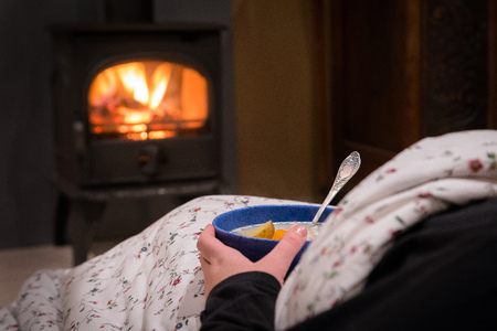 Photo pour Woman having a hot bowl of vegetable soup at the fireplace. Burning fireplace with wooden logs burning inside in the background. Warm light, romantic, christmas like atmosphere - image libre de droit