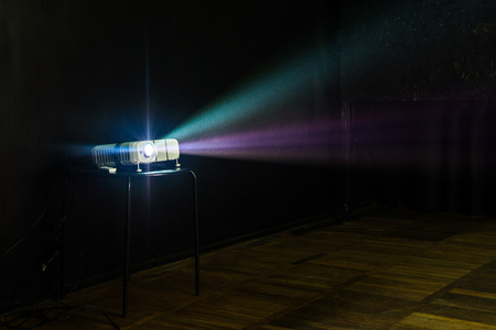 Foto de Close-up of multimedia projector with colourful rays of light projecting on the screen - Imagen libre de derechos