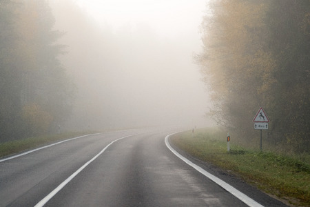 Photo pour Driving on countryside road in fog. Illustration of dangers of driving in bad weather conditions: foggy, hard to see ahead - image libre de droit