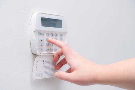 Photo pour Woman hand entering alarm system password of an apartment, house of business office. Surveillance and protection console against rubbery and thief - image libre de droit