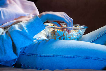 Foto de Close up o f hand waking popcorn from a bowl while watching TV. Person sitting in comfortable couch and watching home cinema in the dark. - Imagen libre de derechos
