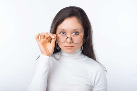 Photo pour portrait of beautiful young woman wearing round glasses and looking confident at the camera - image libre de droit