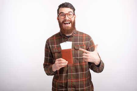 Young male traveler is excited about a new trip while holding his passport and some tickets.