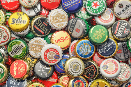 CARANSEBES, ROMANIA - JULY 6, 2014: Background of beer bottle caps, a mix of various european brands.