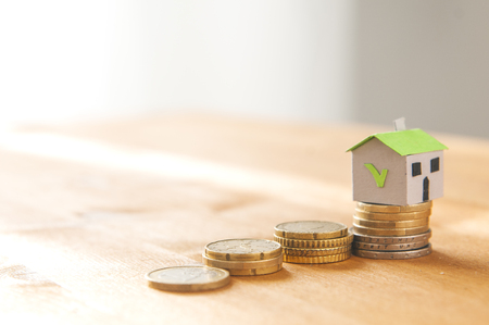 Photo pour A paper house on a coin pile and a stair made of coin: mortgage and loan concept - image libre de droit