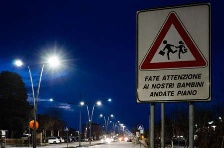 Foto per school pedestrian crossing road sign in Italy with the messagge pay attention to our children, slow down - Immagine Royalty Free