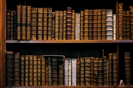 Foto de Ancient tomes on an antique wooden bookshelf - Imagen libre de derechos