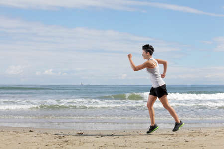young woman with short hair doing sport running on the beach on a sunny day
