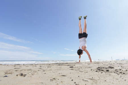young woman with short hair doing exercise standing in hands on the beach on a sunny day