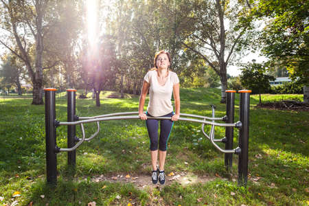 woman doing exercise in park on the sports and fitness equipment