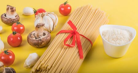 Photo for Spaghetti pasta with ingredients for cooking pasta on a yellow background. Colorful top and closeup view of raw ingredients for Italian dish. Flat lay design concept with copy space for promotion - Royalty Free Image