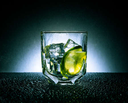 Gin and tonic with ice and lime on a dark background with white spot