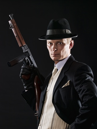 Man like a chicago gangster in suit with Thompson submachine gun