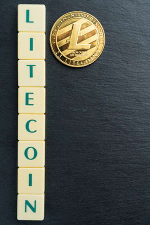 Physical Litecoin gold coin with text made out of letter tiles. Cryptocurrency. Vertical orientation. Copy space on the right.