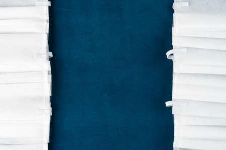 Photo pour White protective face masks on a blue background. Copy space in the center. - image libre de droit