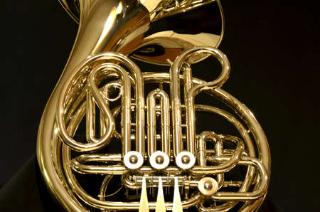 French horn with bell upright on black background