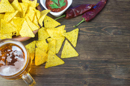 Nachos corn chips with classic tomato salsa. Fresh cold beer is perfect with savory snacks...