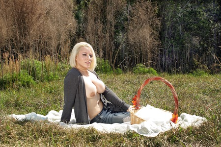 A lovely, busty, topless blonde enjoys a solitary picnic on a bright, sunny day.