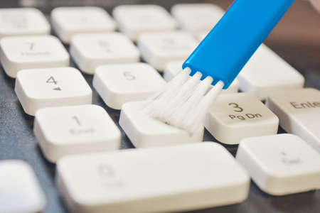 Closeup photo of cleaning and caring computer and computer peripherals. Cleaning the keyboard with white keys with a blue brush. Remove dust from desktop computer ceyboard.