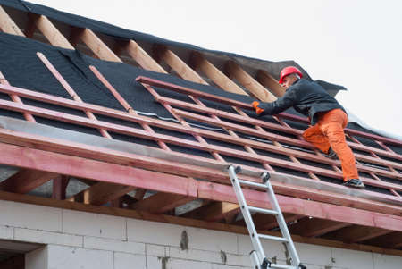 Photo pour Worker installs bearing laths on the truss system - image libre de droit
