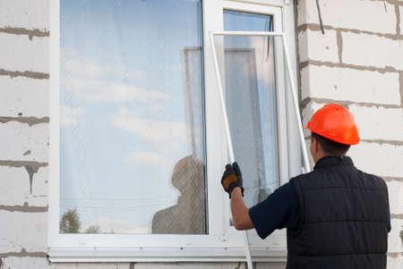 Foto de construction worker sets mosquito net on a plastic windows - Imagen libre de derechos