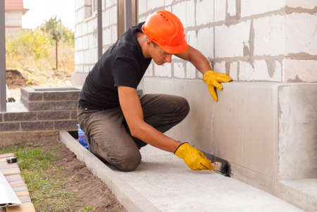 Photo for worker applies bitumen mastic on the foundation - Royalty Free Image