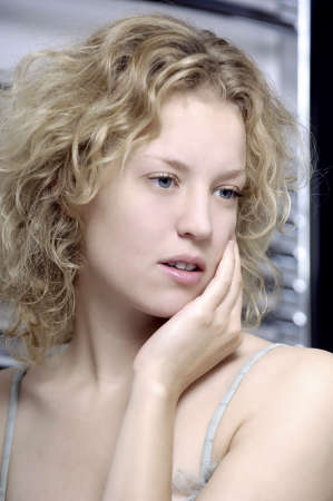 blond woman with one hand caressing her face