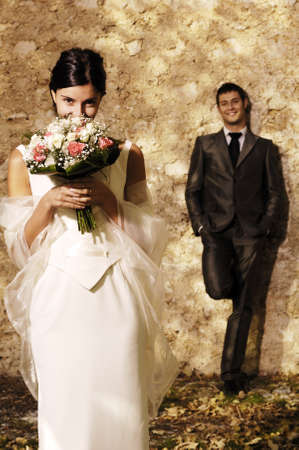 bride with flowers and groom standing behind