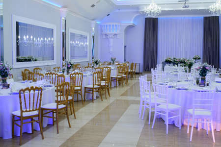 Photo pour The interior of a wedding banquet hall: round tables with white tablecloth and all necessary supplies for dinner on them, bouquet of flowers; gray curtains, beige floor, white walls and ceiling, white and brown chairs - image libre de droit