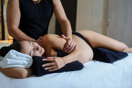 Photo pour Later view of pregnant caucasian young woman lying on a bed and having a relaxing oriental prenatal massage on her arms - image libre de droit