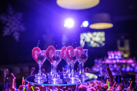 Photo pour Buffet table with snacks, canapes; shrimp with sauce in glasses at a birthday party in blue lights - image libre de droit