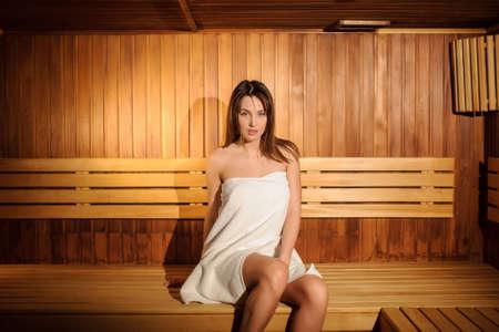 Foto de close up photo of  a beautiful woman wearing a white towel in a wooden sauna - Imagen libre de derechos