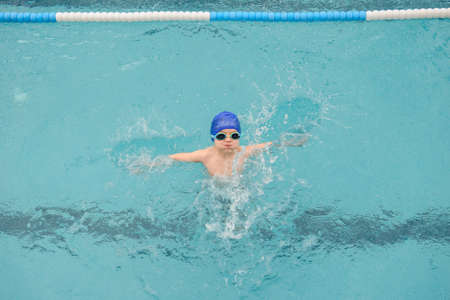 Photo pour top view of a 7-year boy playing and swimming in the swimming pool - image libre de droit