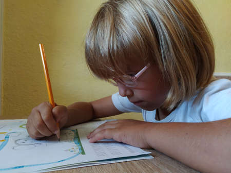 Photo for A 6 or 7 year old girl draws in a book. The child does his homework. Blond hair and pink-rimmed glasses. Training and education concept. - Royalty Free Image