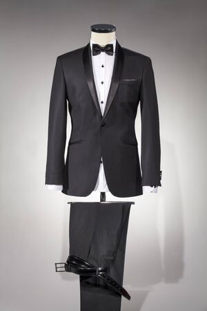 Photo for Male clothing, suit on stand. Men's black suit and white shirt and black bow tie, classic men's shoes and belt isolated on white background. Tuxedo. - Royalty Free Image